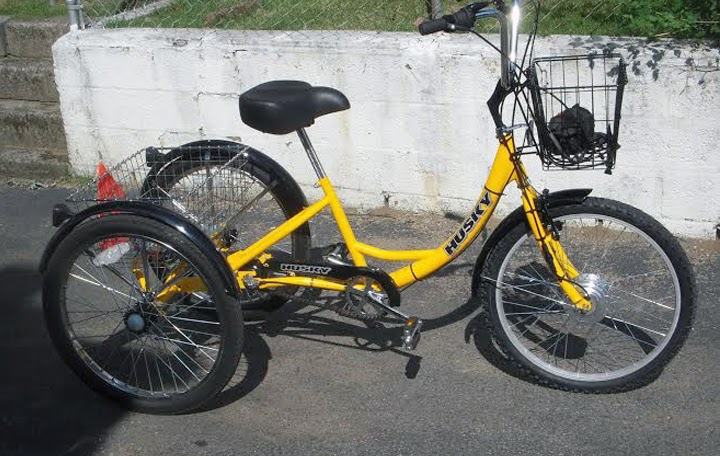 yellow bike with a front-wheel tricycle conversion kit and baskets