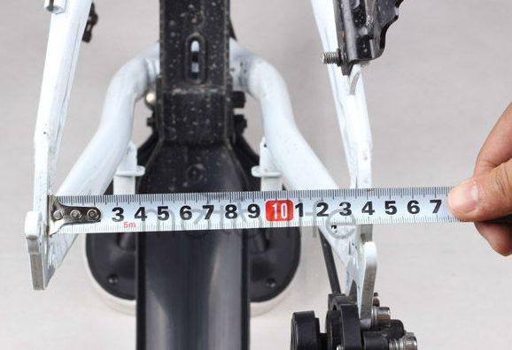 a person measuring a rear wheel bike bracket