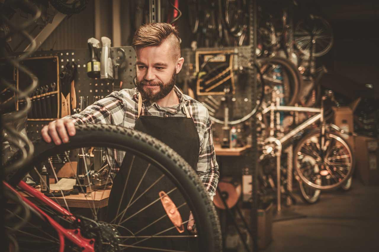 a man demonstrating how to measure a bike wheel