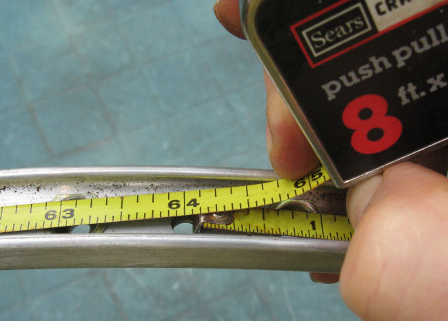 a close-up of a measuring tape around a bike wheel