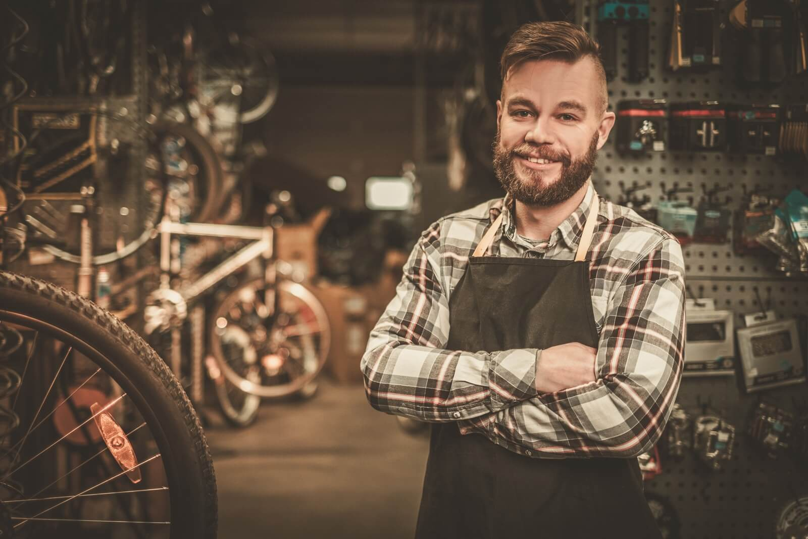 man wearing a plaid shirt and apron standing in a bike shop