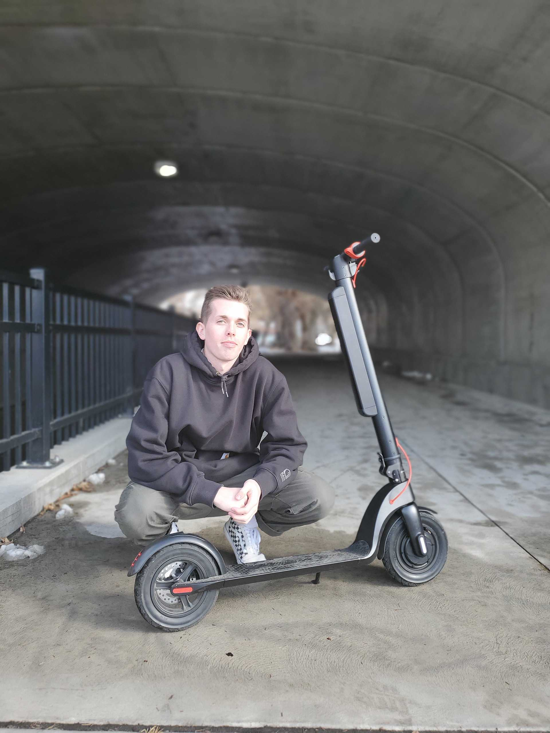 man next to an electric scooter
